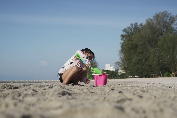 Child playing with toys at beach