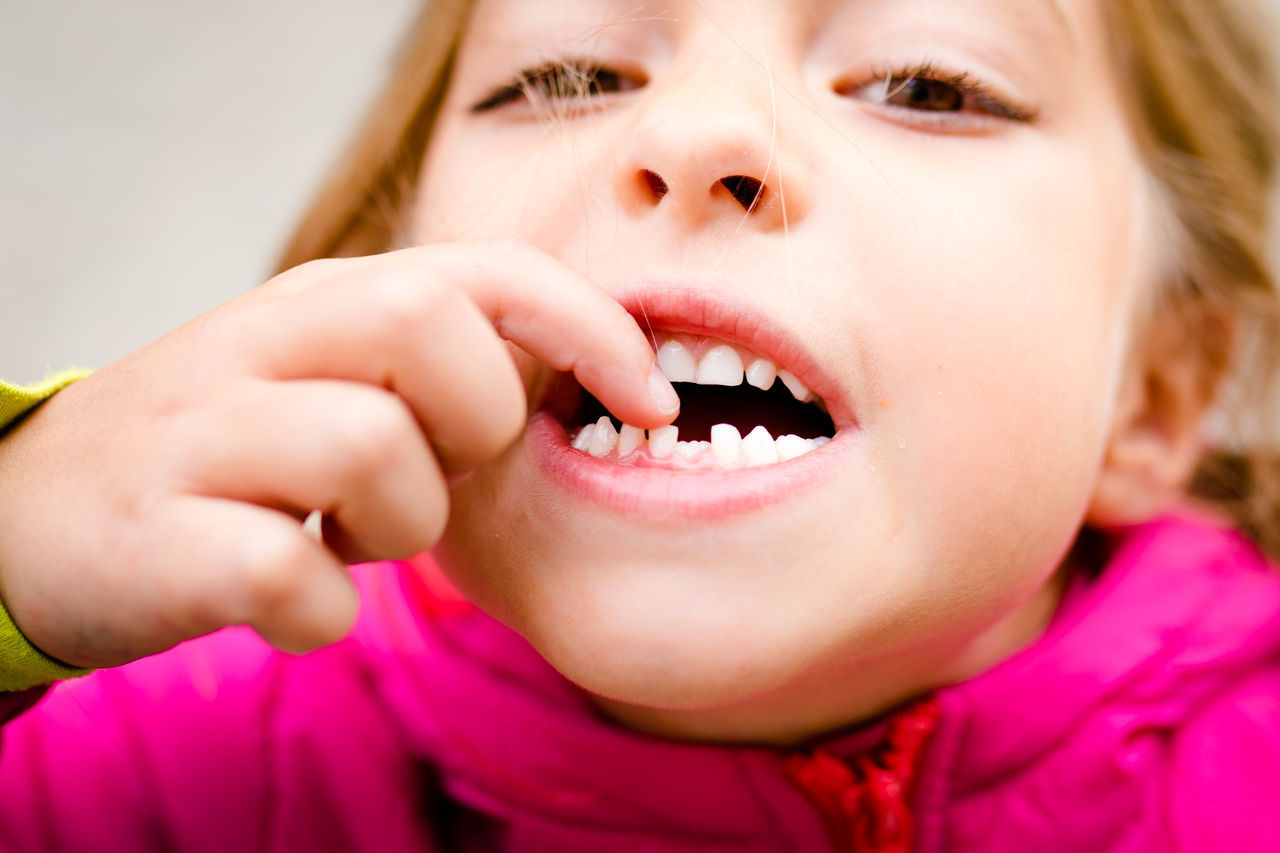 Close-Up Portrait Of Girl Touching Teeth