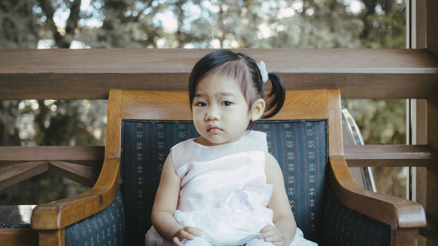 Portrait Of Baby Girl Sitting On Armchair