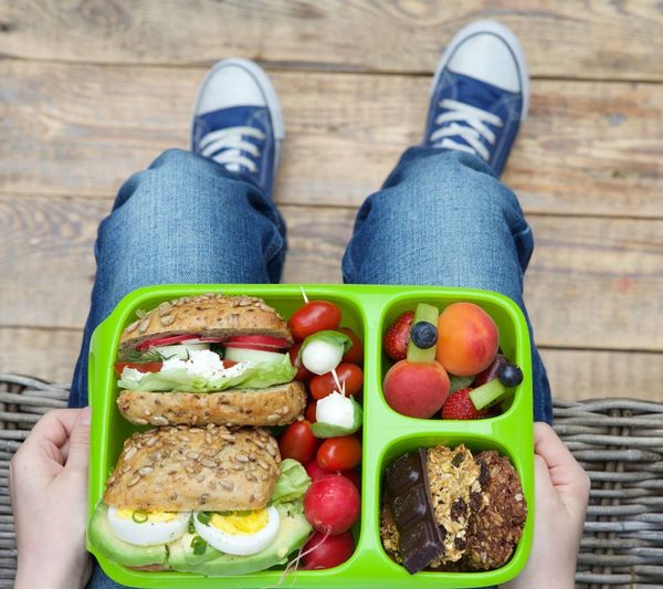 Low section of man sitting with lunch box