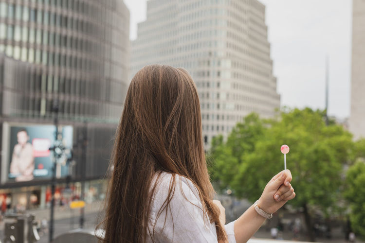 Side view of woman holding lollipop against buildings in city