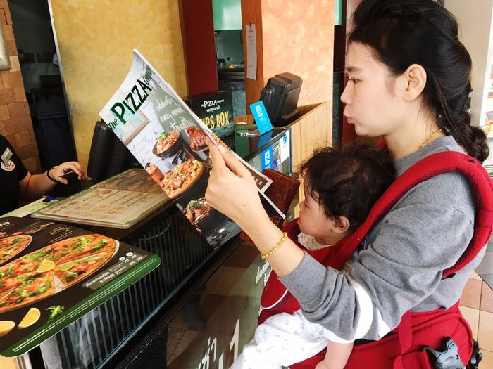 Side view of woman with son reading menu