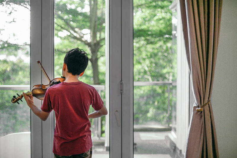Rear view of boy playing violin by window