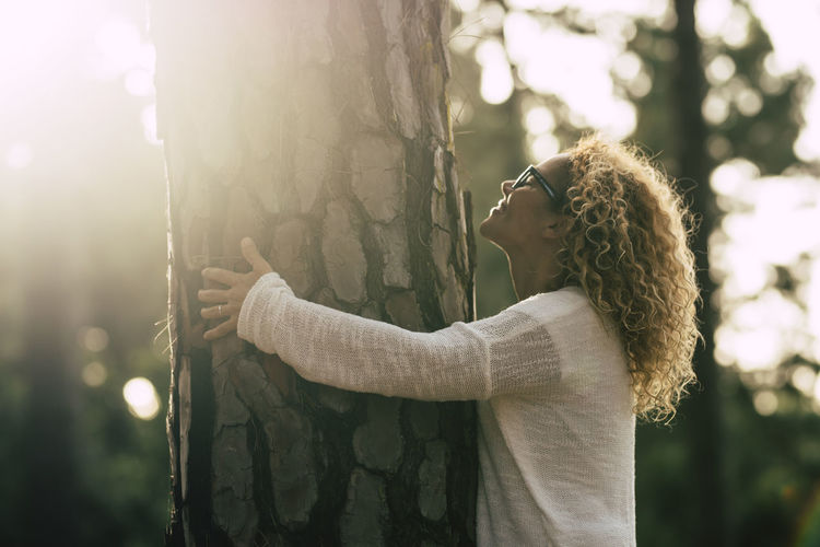 Smiling woman embracing tree trunk