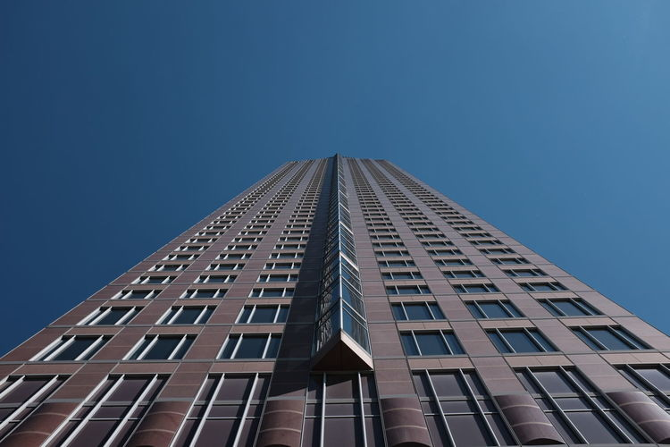 Low angle view of messeturm against clear blue sky