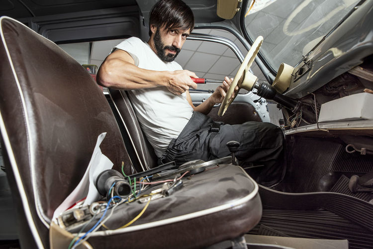 One Person Men Transportation Casual Clothing Land Vehicle Lifestyles Sitting Garage Workshop Work Working Job Labour White T-shirt Old Cars Tunning Repairing Occupation Adult Beard Portrait 40 Years Old Determination Building - Activity Real People