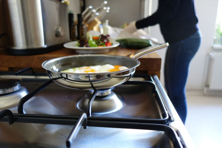 Fried Egg In Pan On Stove While Woman Working In Background At Kitchen