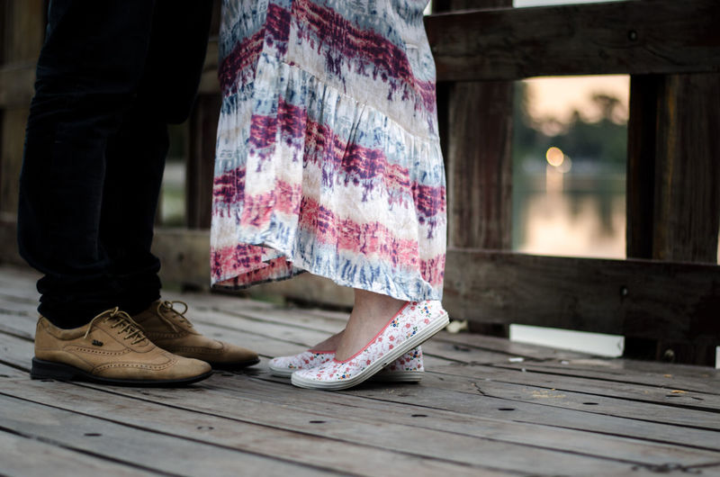 Low angle view of couple standing on wooden pier