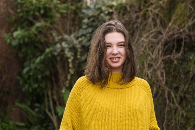 Smiling teenage girl in a yellow sweater outdoors