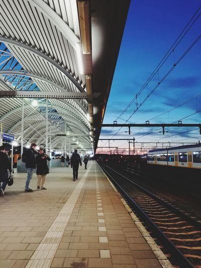 People waiting at railroad station platform against sky