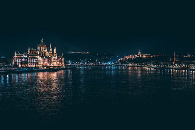 Illuminated Hungarian Parliament Building By River Against Clear Sky At Night