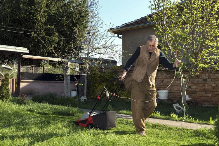 Full length of man mowing at yard