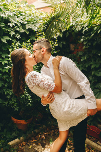 Newly wed couple kissing against plants