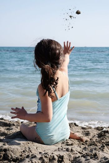 Rear View Of Girl Throwing Sand In Sea While Sitting At Beach Against Clear Sky