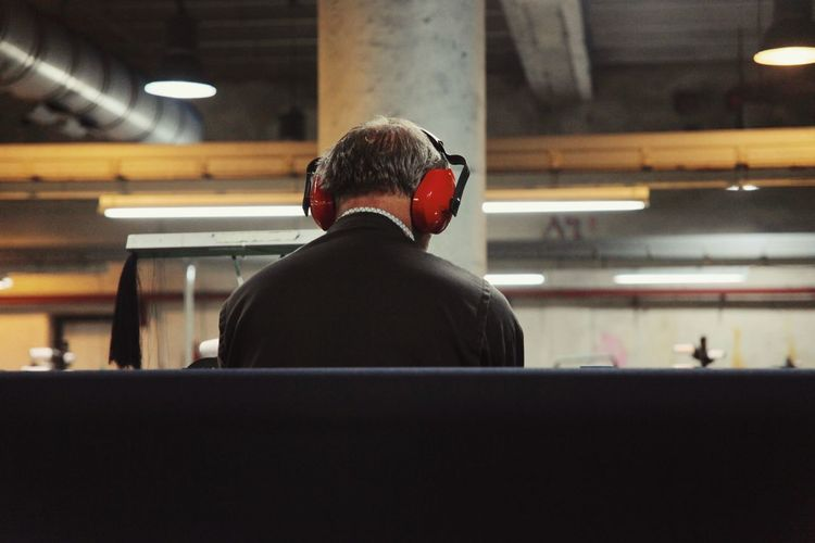 Rear view of man listening to music in textile factory