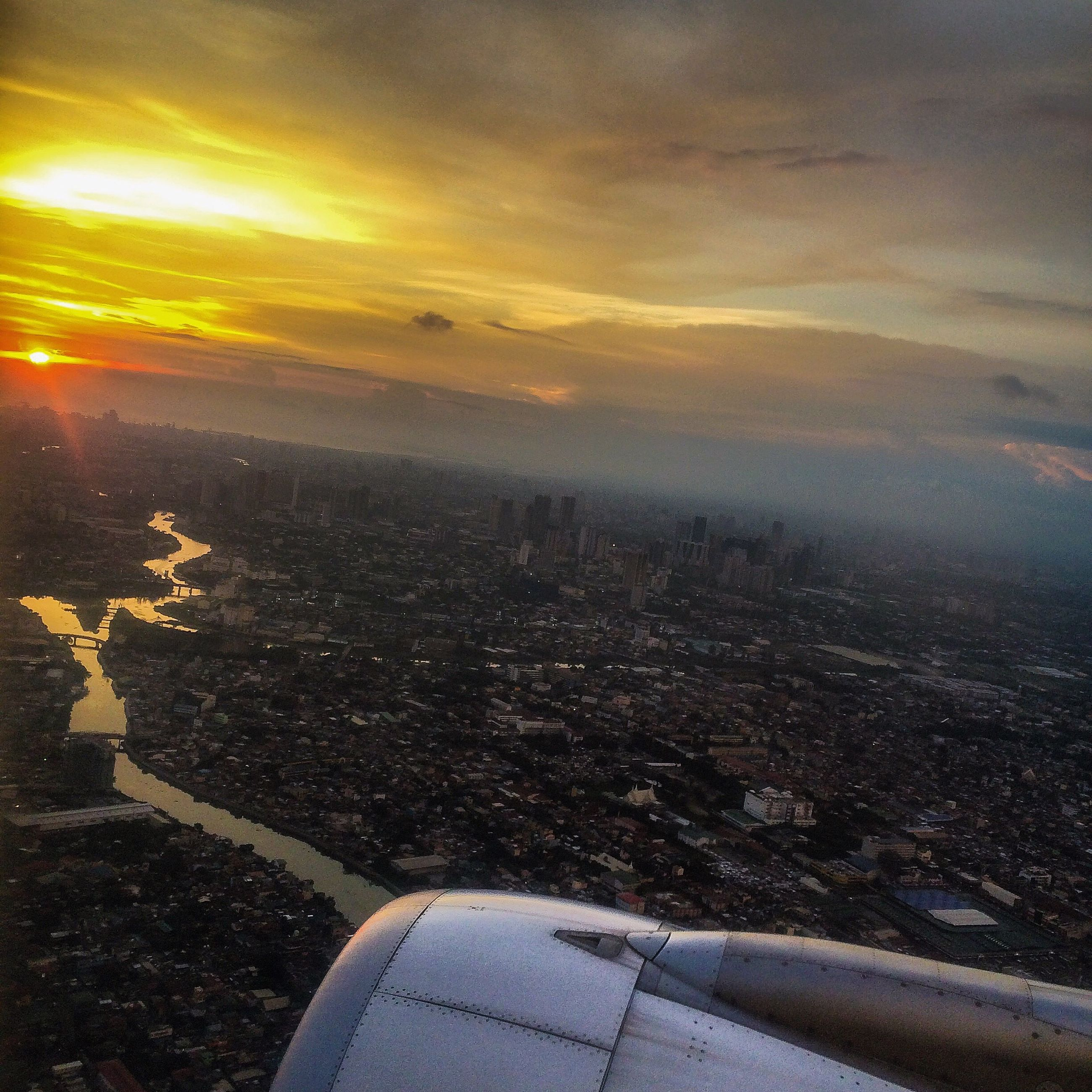sunset, sky, transportation, airplane, aerial view, sun, air vehicle, mode of transport, cloud - sky, landscape, part of, sunbeam, cityscape, aircraft wing, sunlight, flying, city, cropped, scenics, travel
