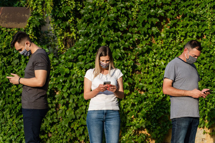 Full length of friends standing on mobile phone