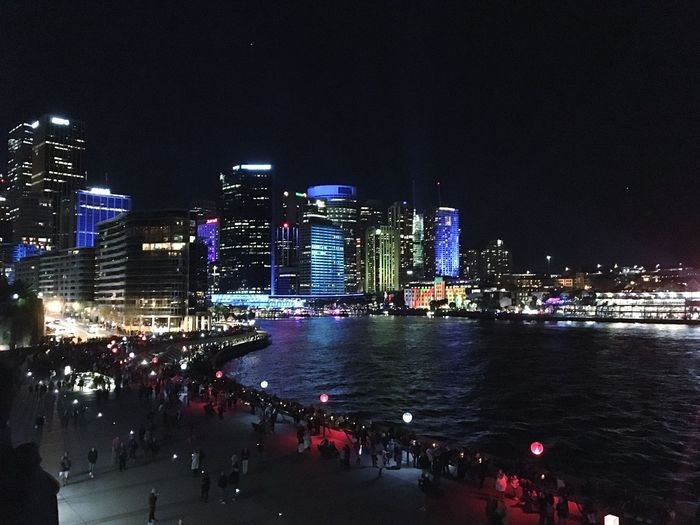 Crowd at promenade by illuminated buildings in city against clear sky at night