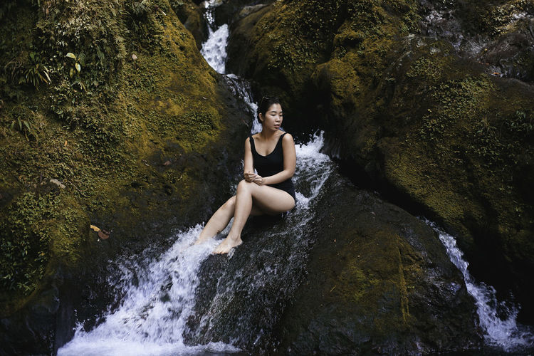 Portrait of young woman sitting on rock by river in forest
