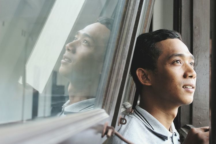 Close-Up Of Smiling Young Man Looking Away Against Window