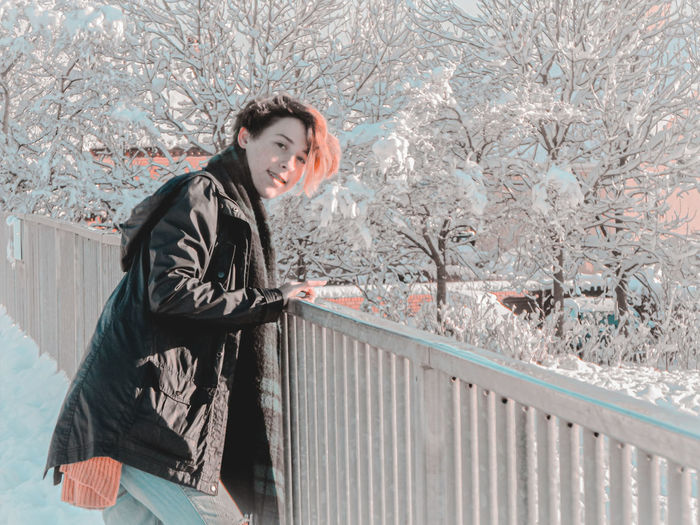 Portrait of smiling woman standing in snow