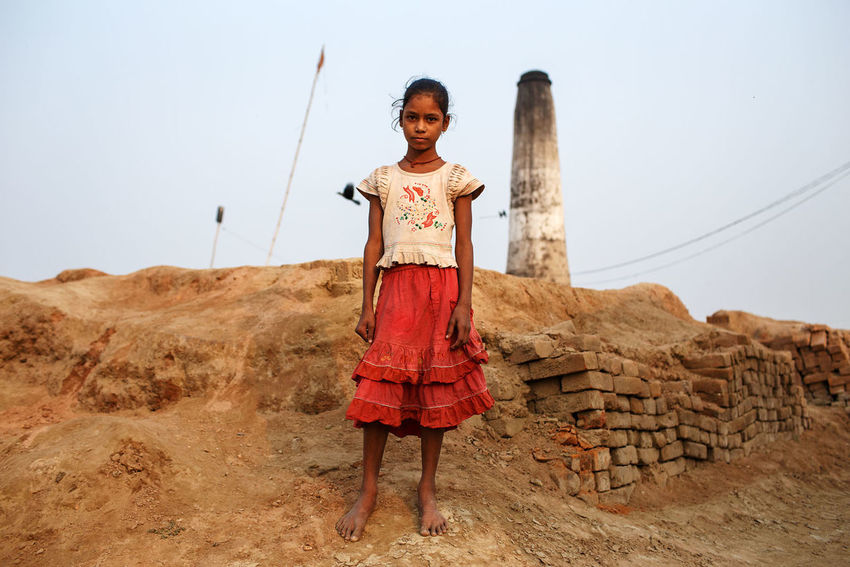 A young girl in a brick kiln in Patna, Bihar state, India, 2013. India Patna Bihar Brick Kiln Bricks Portrait Young Girl Chimney