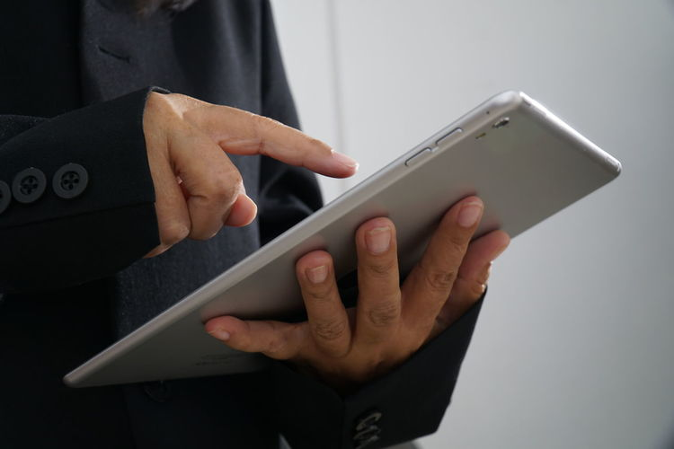 Midsection of businessman using digital tablet at office