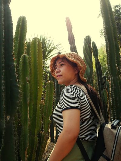 Young woman standing by succulent plant against sky
