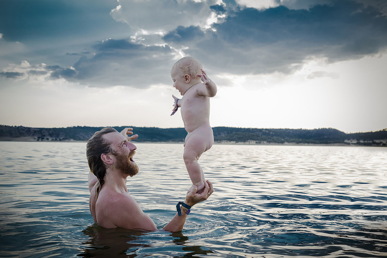 Full length of smiling baby girl with father in sea
