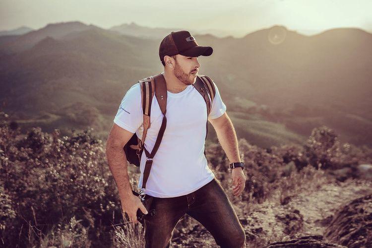 Man wearing cap standing on landscape