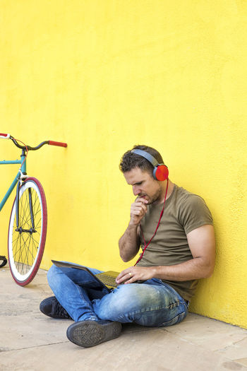 Side view of attractive guy is sitting on the floor with trendy look, writing in notebook using computer, having headphones while looking at screen against a yellow wall One Person Casual Clothing Wall - Building Feature Young Men Young Adult Full Length Yellow Lifestyles Real People Leisure Activity Bicycle Transportation Sitting Men Copy Space Looking Activity Architecture Outdoors Young Man Hipster Trendy Fashionable Hat T-shirt Sitting Headphones Bike Fixie Laptop Using Laptop Vintage Side View