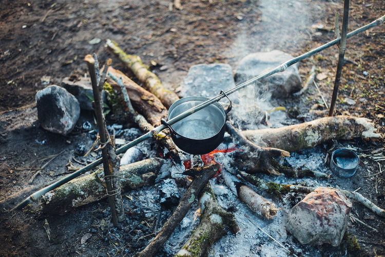 High angle view of cooking pot over burning fire at campsite
