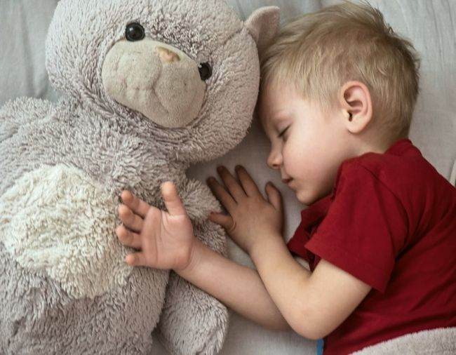 Close-up of boy sleeping with teddy bear on bed