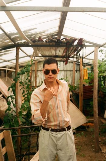Portrait of young man standing in greenhouse