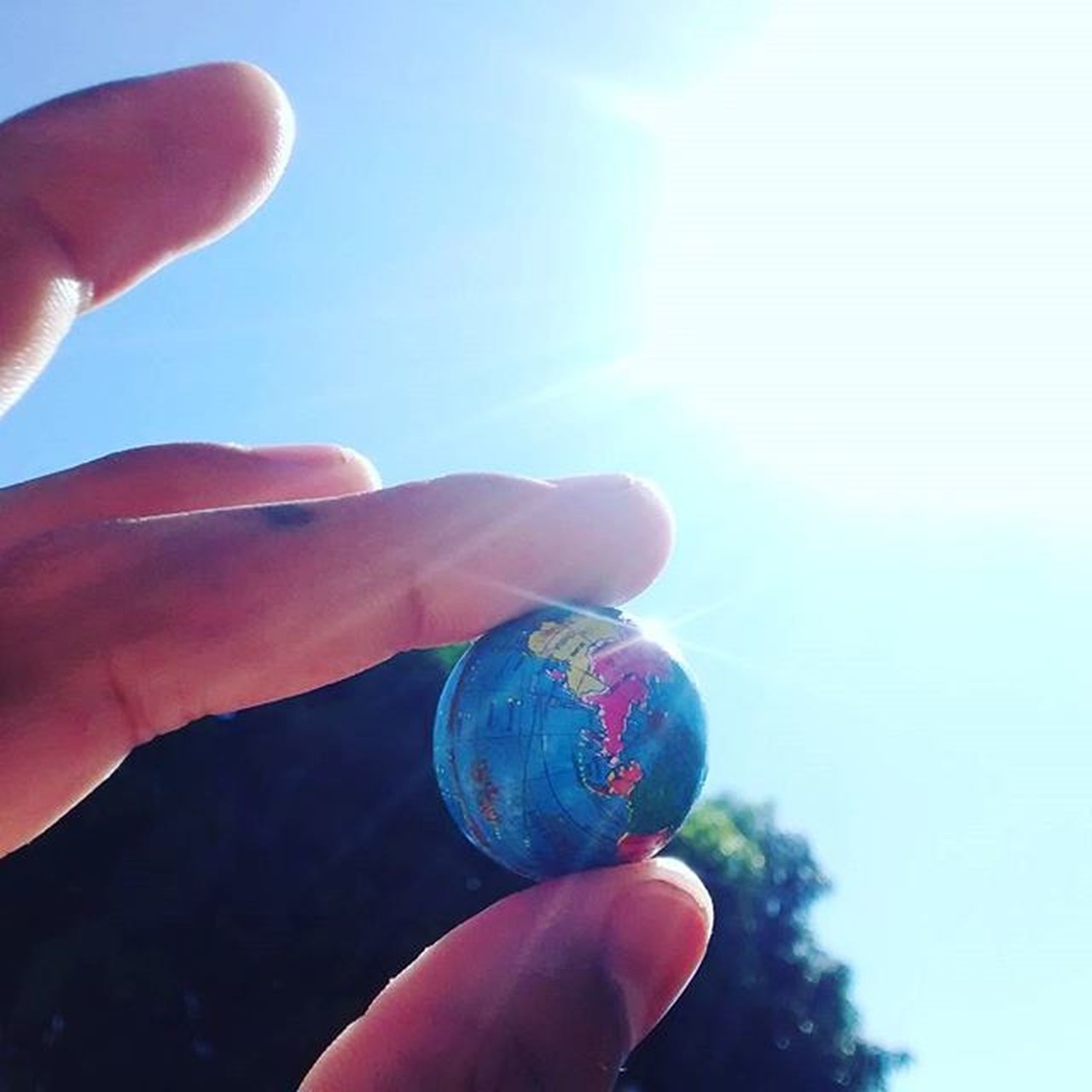 human hand, human body part, human finger, holding, one person, real people, personal perspective, sky, close-up, sunlight, blue, outdoors, day, planet earth, nature, space, people, adult