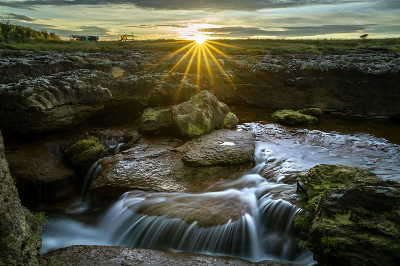 Stream flowing through rocks against sky during sunset