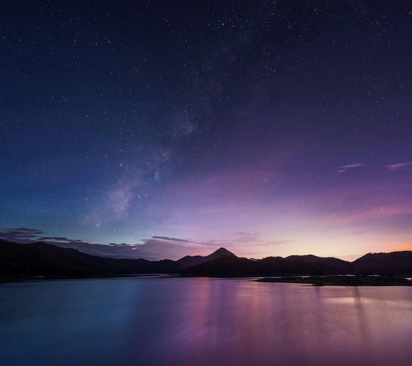 Long exposure shot of milky way over majestic mountain lake