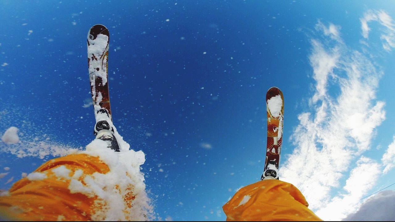 Low section of person skiing against blue sky