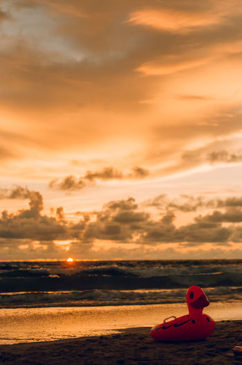 Rubber duck on beach against sky during sunset