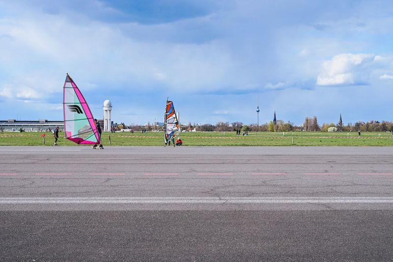 People at airport runway against sky in city