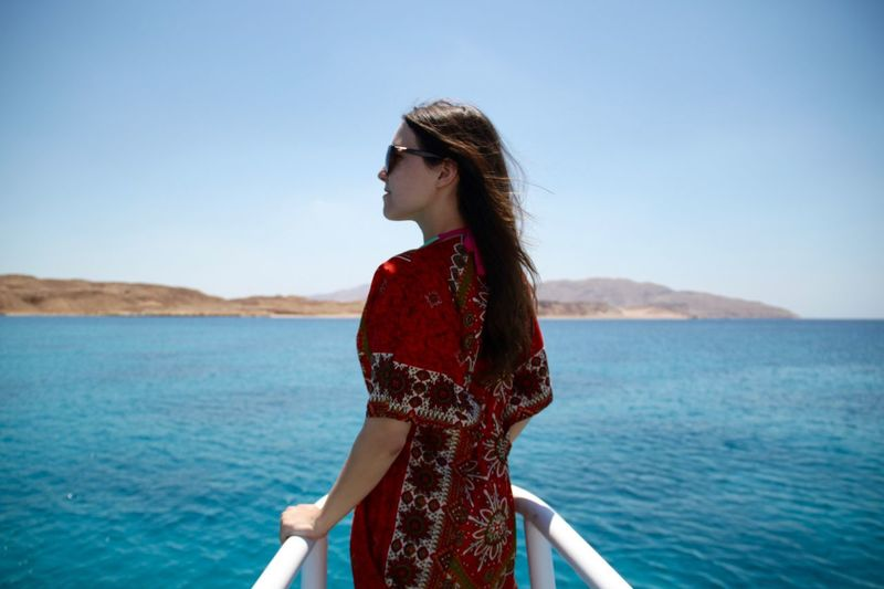 Rear view of young woman standing on yacht bow sailing on red sea