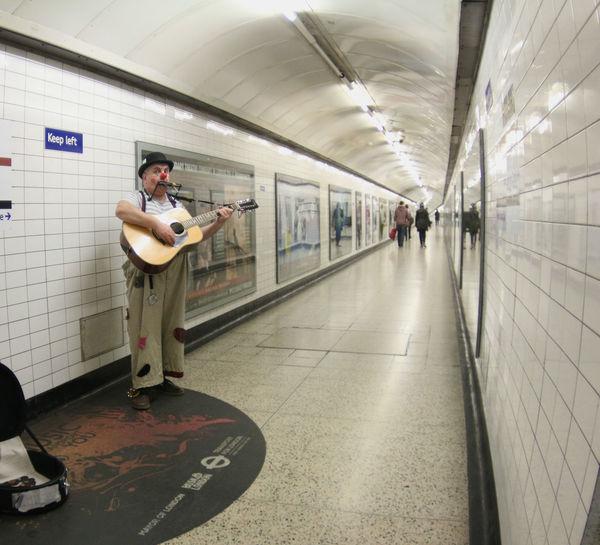 Man playing guitar in subway