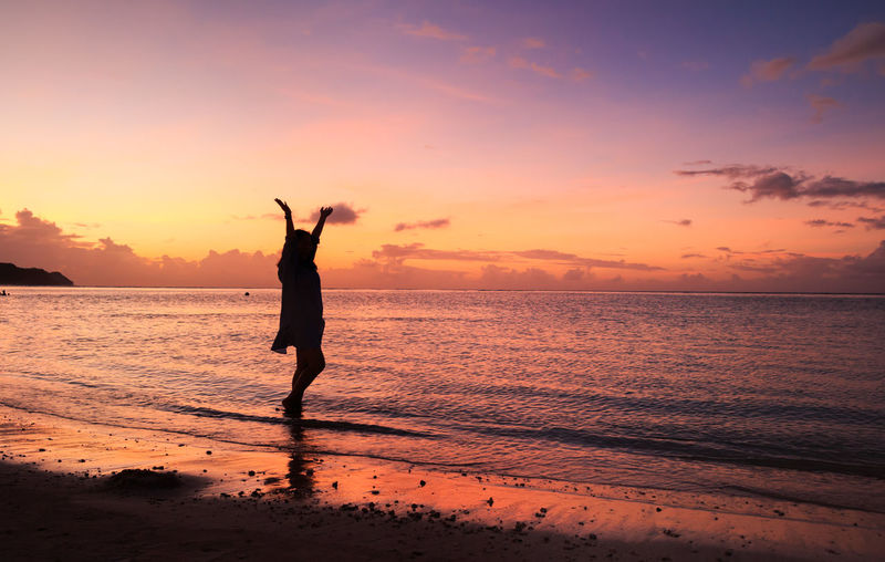 Silhouette woman with arms raised standing at beach against orange sky