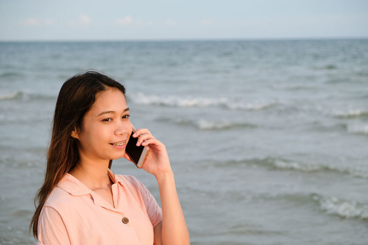 Portrait of young woman standing on beach