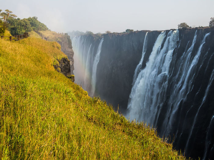 Scenic View Of Victoria Falls With Lush Green And Yellow Grass Against Sky
