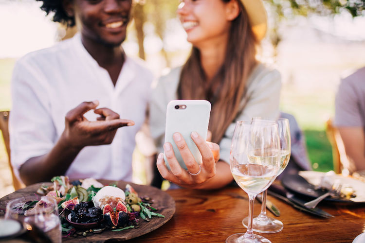 Wireless Technology Communication Food And Drink Mobile Phone Smart Phone Table Technology Young Adult Real People Portable Information Device Food Adult Connection Holding Glass Women People Young Men Alcohol Outdoors
