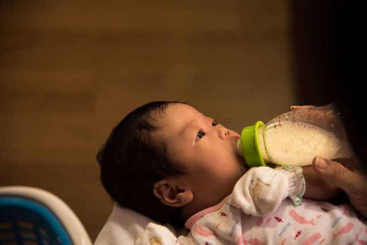 Cropped hand feeding baby using milk bottle at home