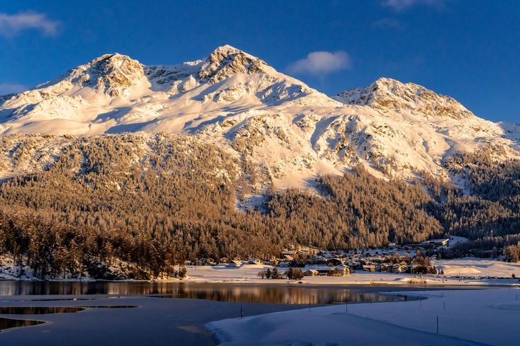 View of beautiful snow mountains behind lake silvaplana and its village in switzerland during winter