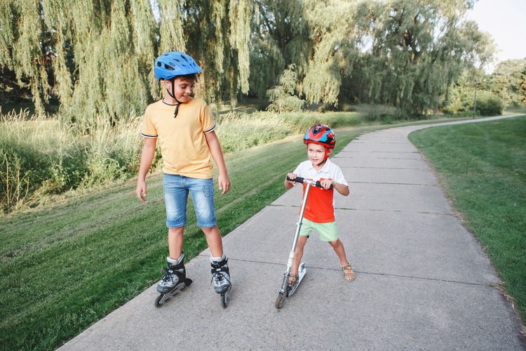Caucasian boys brothers in helmets riding roller skates and scooter. siblings friends relationships.