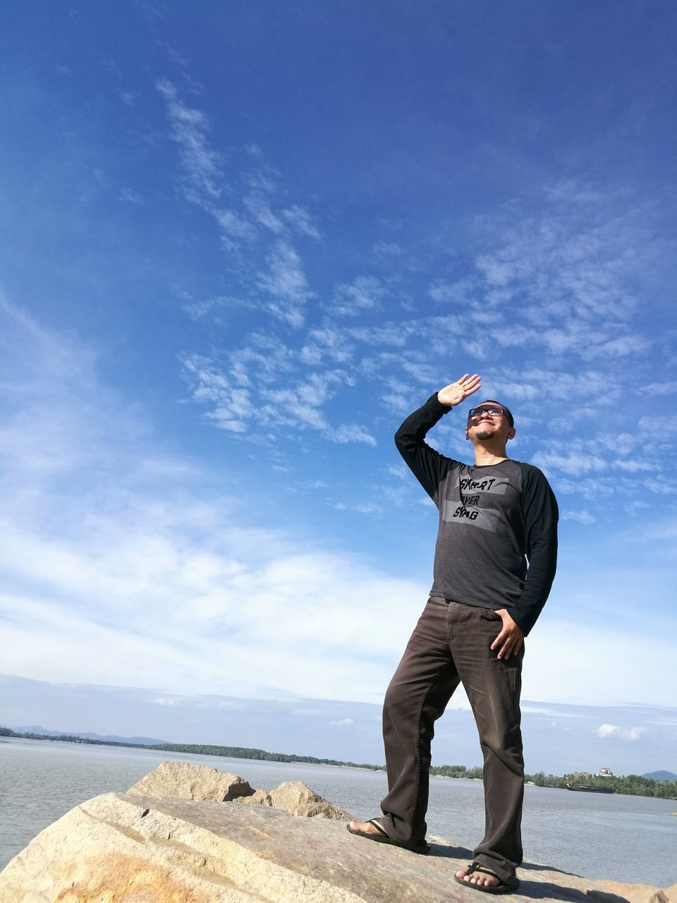 Full Length Of Man Standing On Rock By Lake Against Sky